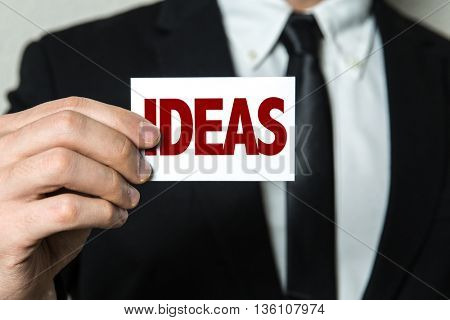 Business man holding a card with the text: Ideas