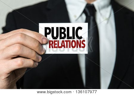 Business man holding a card with the text: Public Relations