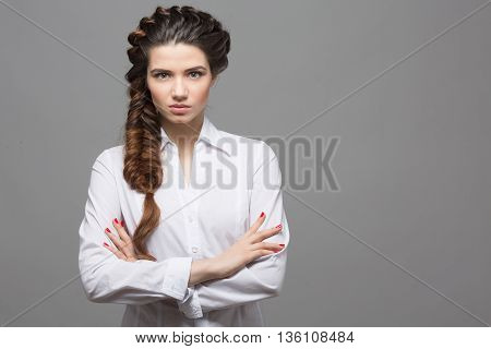 Portrait of beautiful woman with braids posing over grey background. Female lady with modern hairstyle in studio.