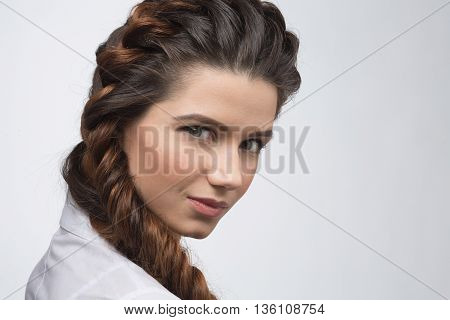 Hair braid. Beautiful woman with healthy long hair. Hairdressing. Hairstyle. Closeup portrait of beautiful woman smiling while demonstrating modern hairstyle in studio.