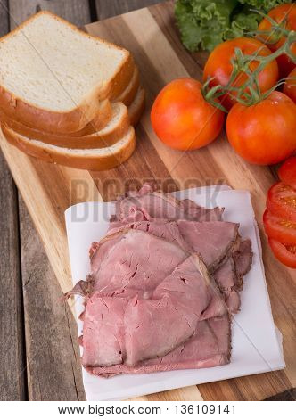 Roast beef with sliced bread tomatoes and lettuce on a cutting board