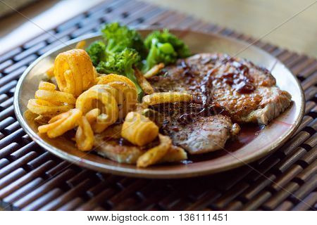 Grilled pork chops with curly fries and steamed broccoli