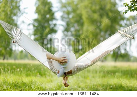 Young Woman Sitting In White Hammock. Rear View.