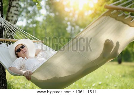 Woman In Glasses Relaxing In The Hammock Outdoors.