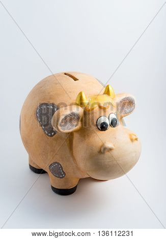 A piggy bank thats actually a cow looking a bit damaged and dirty.