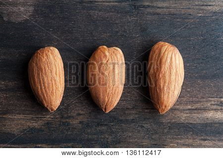 Three Almonds On Wooden Table Closup