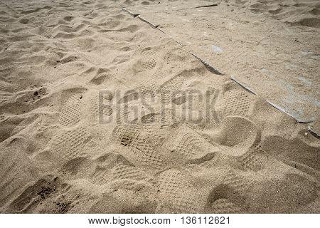 footprints in the sand of an italian beach