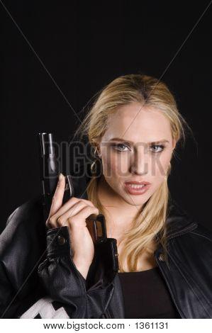 Loira sexy com arma na jaqueta de couro