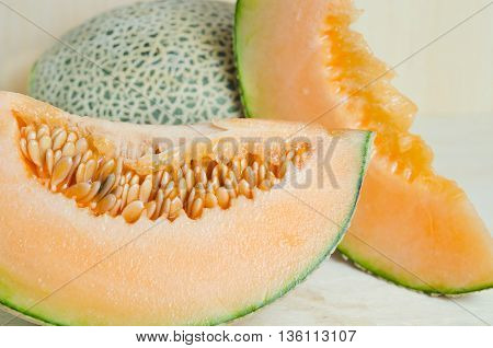 Cucumis melo or melon with half and seeds on wooden plate (Other names are Melon cantelope cantaloup honeydew Crenshaw casaba Persian melon and Santa Claus or Christmas melon)