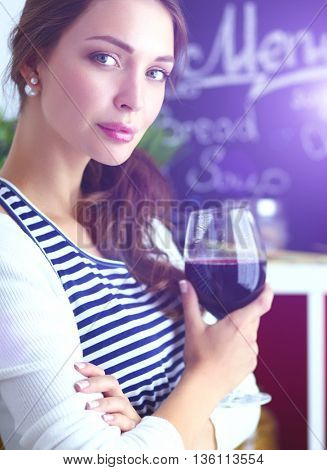 Pretty woman drinking some wine at home in kitchen