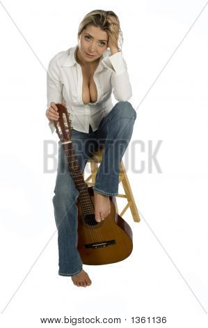 Female Guitarist Sitting On Stool Smiling