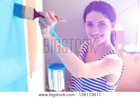 Happy smiling woman painting interior wall of new house