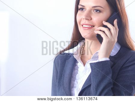 Smiling businesswoman talking on the phone at the office