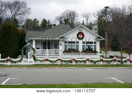 HARBOR SPRINGS, MICHIGAN / UNITED STATES - DECEMBER 24, 2015: A Harbor Springs home, with a stone chimney and a white picket fence, is decorated for Christmas with garlands, ribbons and wreaths.