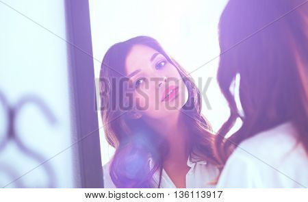 Young woman looking herself reflection in mirror at home