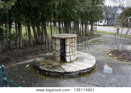 HARBOR SPRINGS, MICHIGAN / UNITED STATES - DECEMBER 24, 2015: Fresh water flows continuously through an artesian well at Tuttle Corner in Harbor Springs.