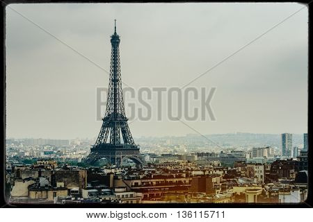 The Eiffel Tower in Paris, France. Vintage look with film grain, darkroom style frame, and light leak.