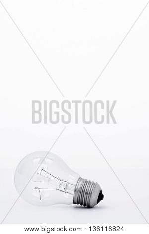 A used light bulb resting on its side with a white background.