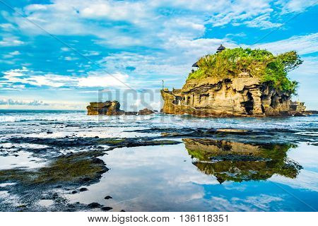 Tanah Lot Temple is a Hindu Temple on the Island of Bali,Indonesia. Seen here in the morning with a reflection over pool of water.