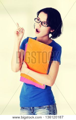 Student woman with coloured note pad pointing up.