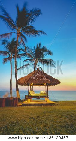 A beach hut overlooking the ocean at sunset with palm trees swaying in the wind and an orange glow over the horizon.