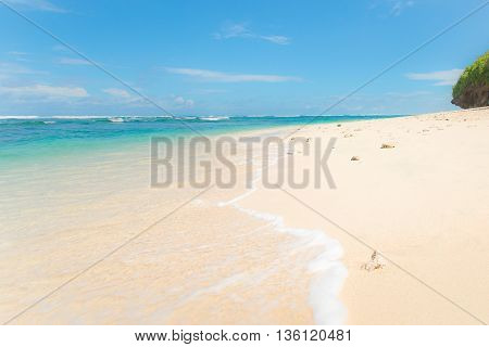 A wave washing ashore of a beautiful white sandy tropical beach. Bali Indonesia