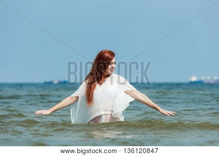 Vacation. Girl in ocean water. Young woman having fun relaxing on the sea. Summertime.