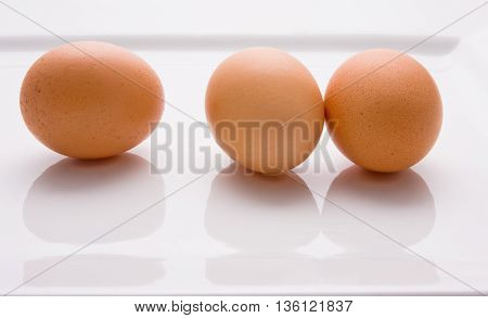 Three eggs lying on their sides on a plate