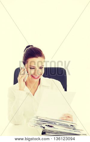 Beautiful business woman sitting and talking through phone.