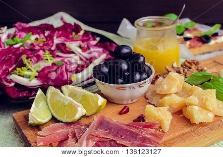 Sliced prosciutto with vegetable chicory salad cheese and olive. Appetizers set. Table full of mediterranean appetizers tapas or antipasto. Italian food. Selective focus.
