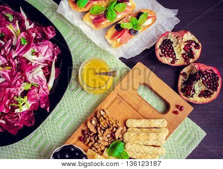 Chicory salad with appetizers set: prosciutto pomegranate olives nuts cheese and bruschetta on dark wooden background. Italian food. Top view horizontal