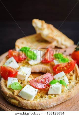 Italian appetizer Friselle. Italian dried bread Friselle on wooden board with tomatoes cherry basil and pepper. Italian food. Healthy vegetarian food. Antipasti concept. Selective focus.