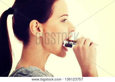 Casual beautiful woman trying to eat blister of pills.