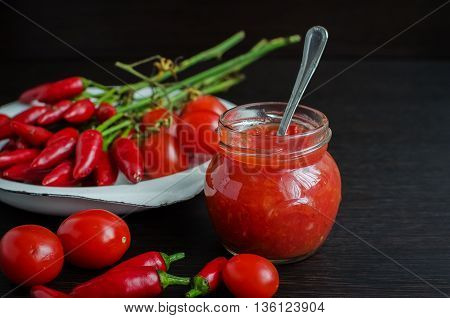 Glass jar of homemade tomato sauce with fresh ingredients on dark wooden background. Natural homemade sauce of tomatoes peppers and vegetables. Chilli jam. Selective focus.