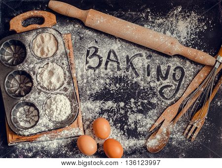 Baking concept on dark background. Baking preparation top view of variety of baking utensils with different kind of flour eggs and word baking on chalkboard. Baking ingredients. Top view.