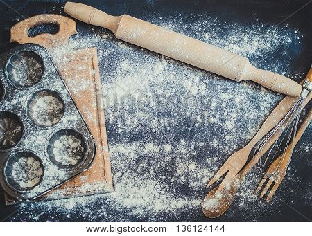 Baking concept on dark background. Baking preparation top view of variety of baking utensils with flour. Kitchen table ware rolling pin. Background layout with free text space. Top view. Copy space.