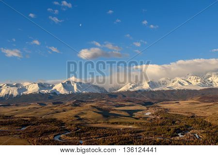 Scenic view with the beautiful mountain peaks with snow and glaciers blue sky clouds and the valley in the sunlight at sunrise