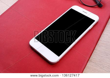 smartphone on red book and glasses on wooden background
