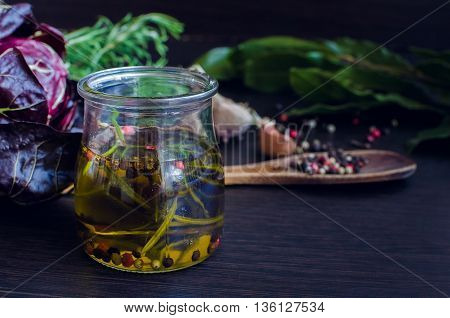 Olive oil with rosemary garlic chicory and pepper. Olive oil in bottle with rosemary and spices on a brown table. Olive oil flavored with spices and other ingredients. Selective focus.