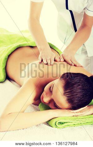 Beautiful woman lying on bed in spa salon.