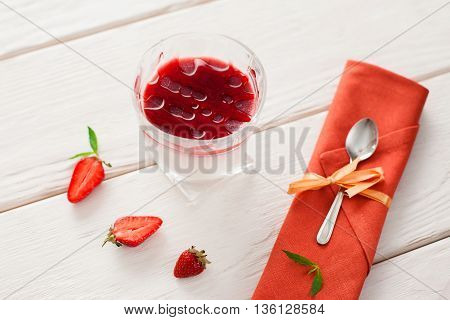 Strawberry organic panna cotta in glass with spoon flat lay. Dessert panna cotta with fresh strawberry slices served in glass and spoon on orange napkin on white wooden table