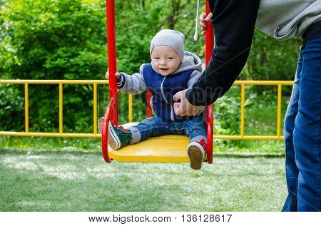 Father swinging his baby. Father and son on a swing in a park. Happy father pushing toddler boy on swing in playground. Smiling little boy sitting on a swing father pushing. Happy family.