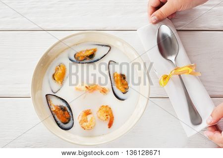 Seafood soup-puree serving flat lay. Top view on bowl with soup-puree with mussels and shrimps and waiter hands, putting napkin with spoon on white wooden restaurant table.