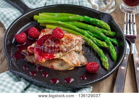 Pork cutlets with raspberry sauce and asparagus in iron cast pan horizontal