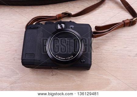 Digital black color camera on wooden background