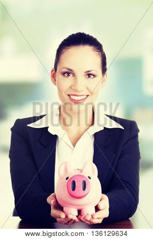 Happy business woman with her savings at the desk
