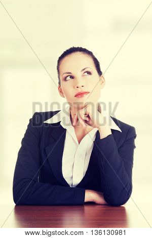 Pretty business woman in sitting at the desk and thinking