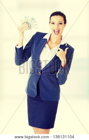 Happy attractive businesswoman holding euros