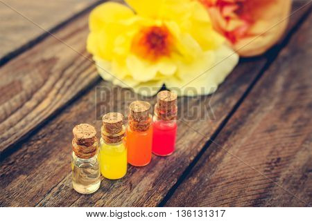 Bottles of essential oil and roses on old wooden background. Toned image.