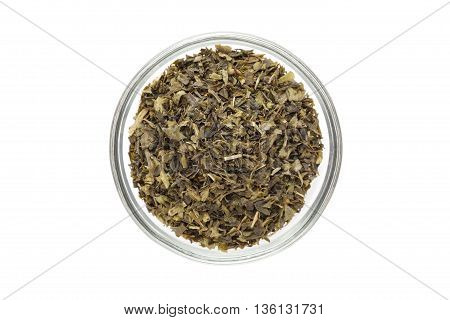 Organic Green tea (Camellia sinensis) Tea bag cut, dried leaves, in glass bowl isolated on white background. Macro close up. Top view.